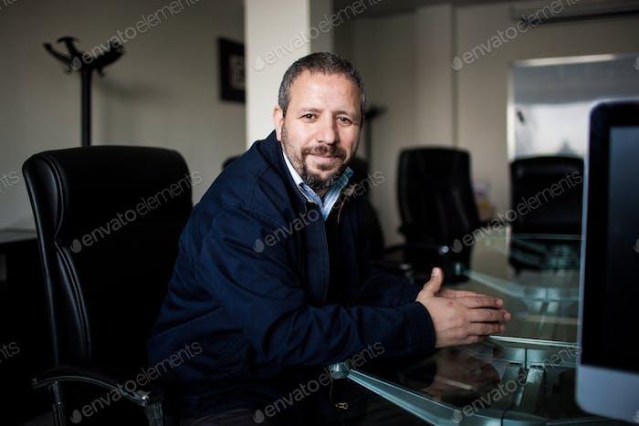 Man teacher in his forties sitting in meeting room