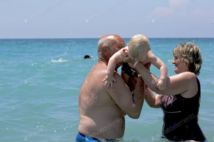 Senior lifestyle. Grandparents swimming in the sea with their grandson. Summertime. Happiness.
