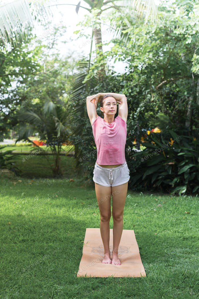 Athletic girl doing yoga exercises, stretching back on open air meadow on green meadow grass in summ