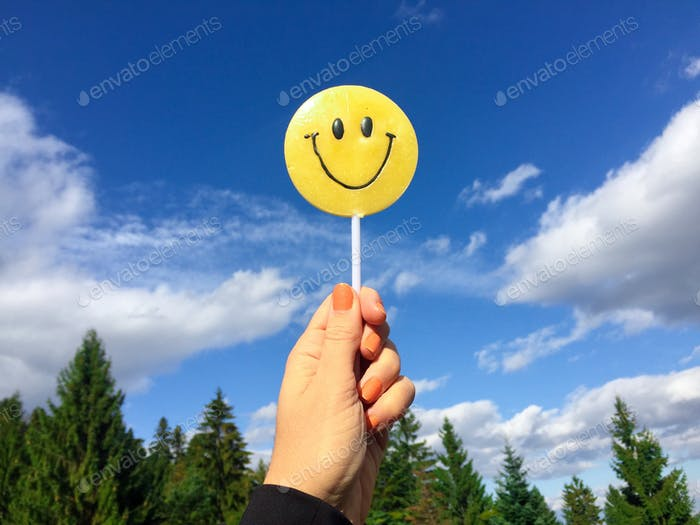 Woman's hand holding smiley face candy with blue sky in the background