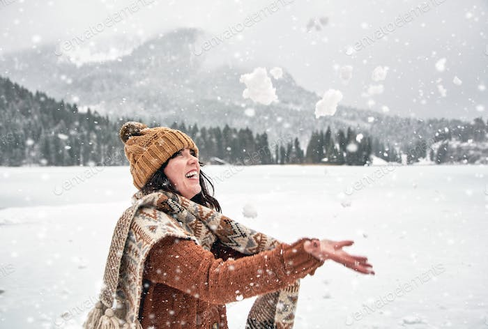 Happy young woman throwing snow in air, outdoors, winter, cold weather, smiling.