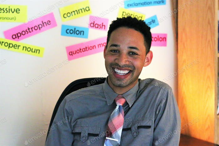 A young diverse teacher sitting in his classroom in front of a board with vocabulary words