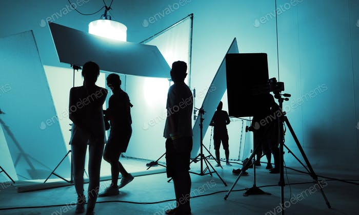 Shooting studio for photographer and creative art director with production crew team setting up ligh