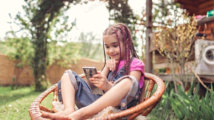Mädchen chatten mit Freunden mit Smartphone, virtuelles Spiel während der Lockdown und nach, neue normale captu