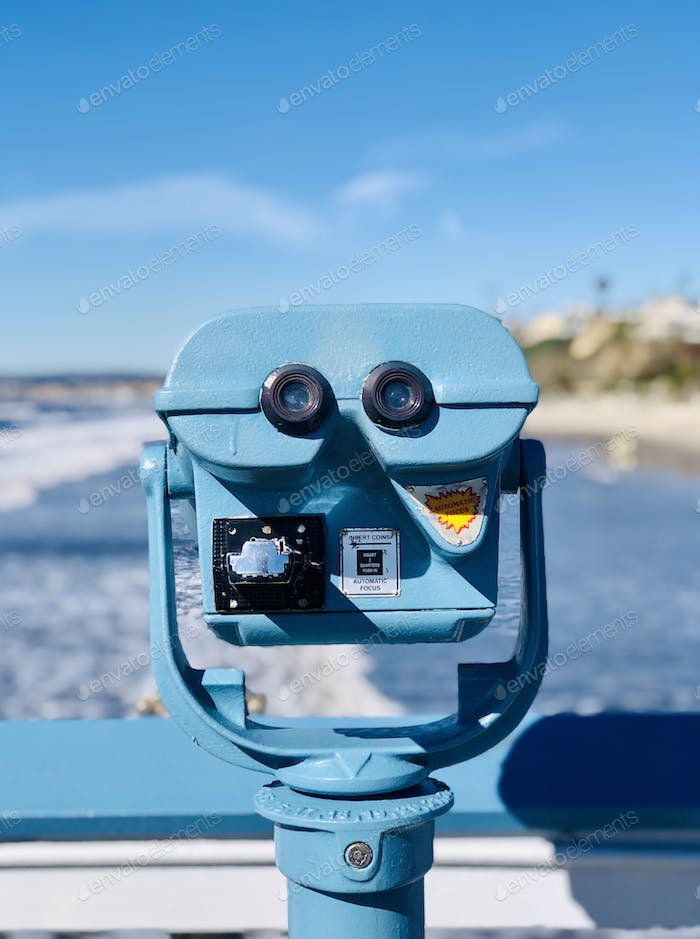 Blue viewfinder on pier  with ocean in background