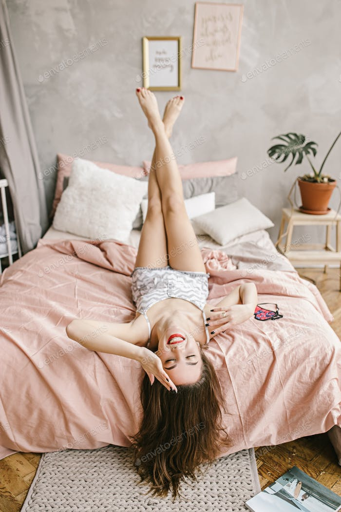 Young girl with long hair is lying on her pink bed and rising her foot up