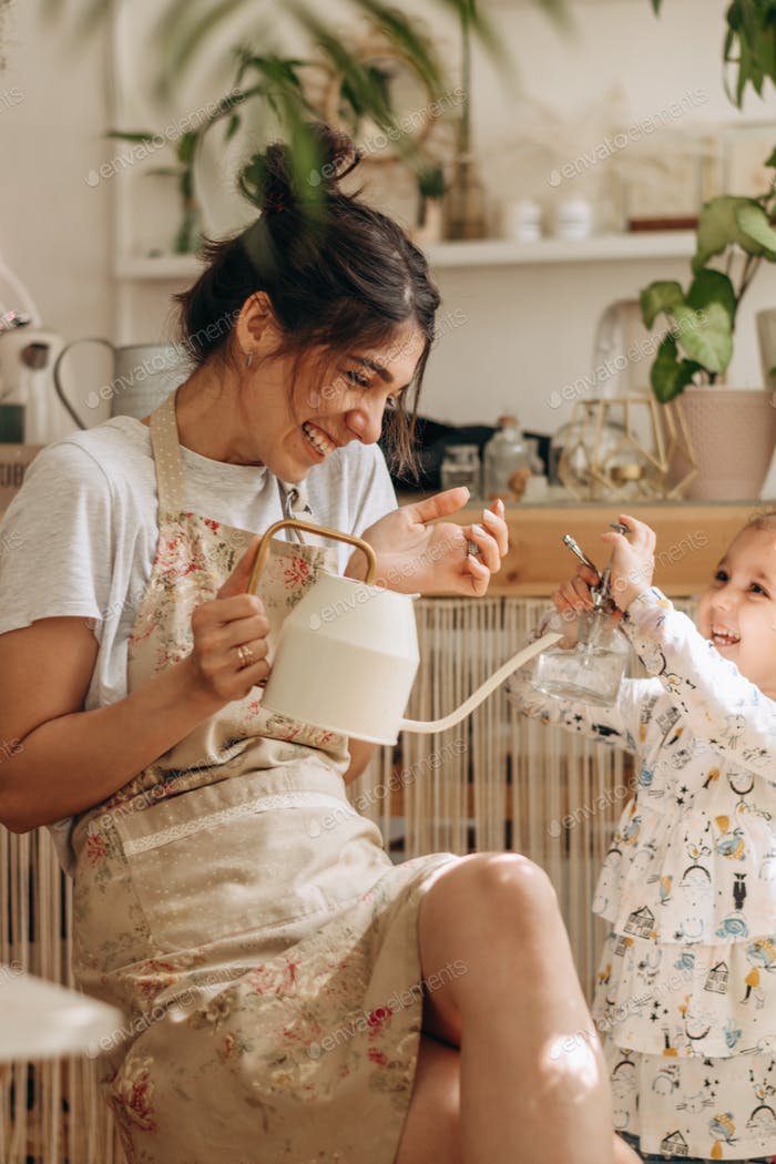 Woman with a daughter watering indoor plants at home and having fun.Home gardening.Family concept.