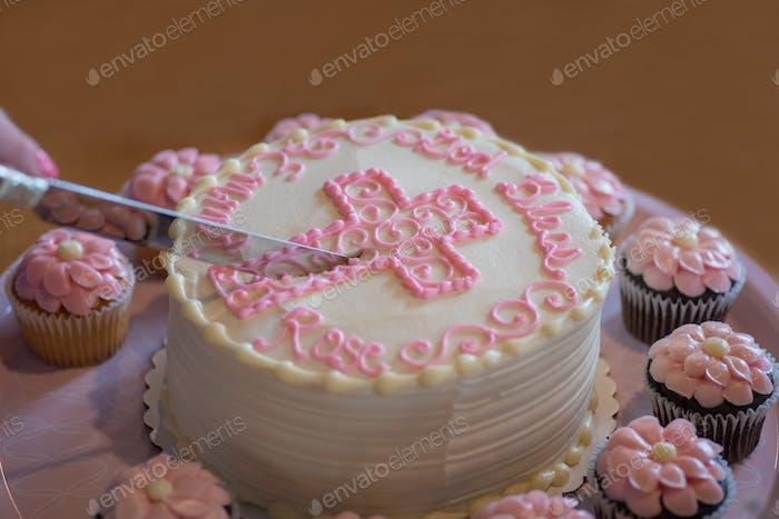 Einen wunderschön dekorierten Taufkuchen schneiden