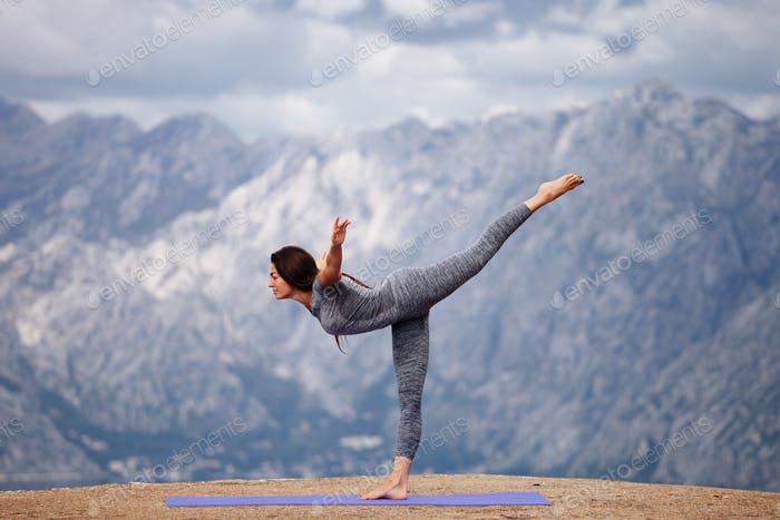 Woman yoga practice in mountains with beautiful view. Yoga workout