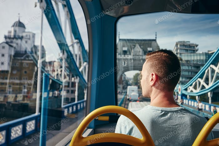 Young man looking through window from double decker bus. City life in London, United Kingdom.