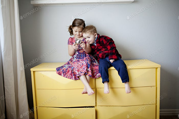 two kids sitting on a yellow dresser and hugging
