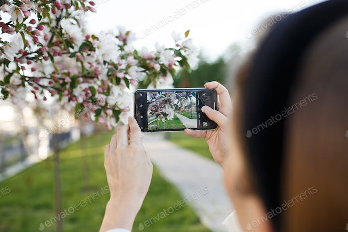 beautiful lovely girl walks alone takes a selfie talking and typing on the phone in the park