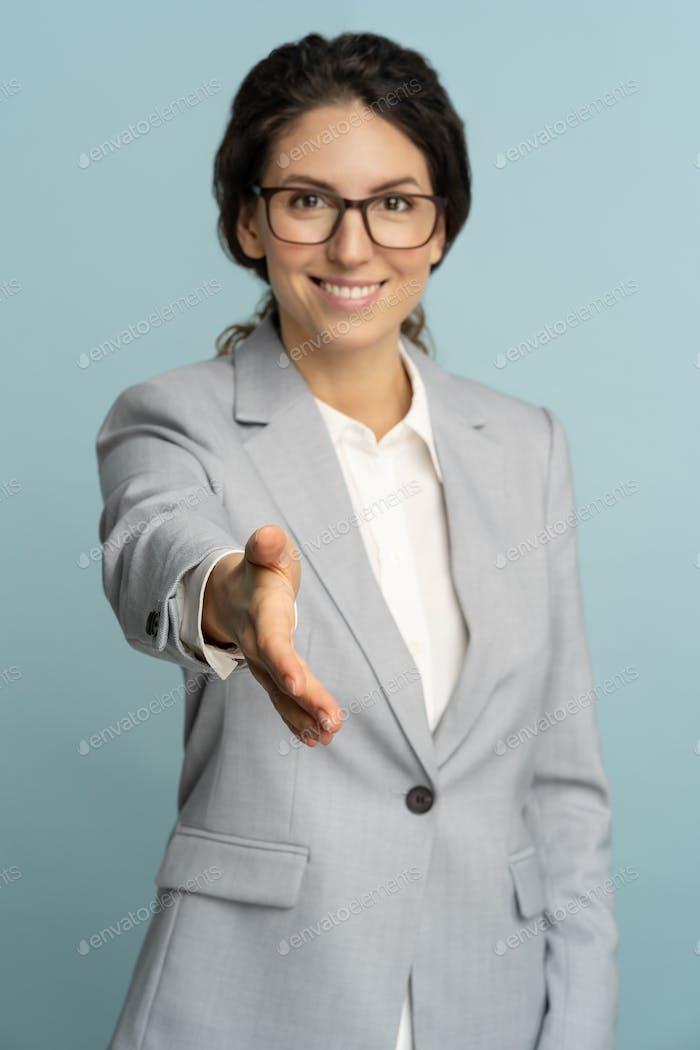дружелюбная гостеприимная веселая деловая женщина или офисный работник носят блейзер, давая руку рукопожатию