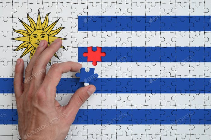 Uruguay flag  is depicted on a puzzle, which the man's hand completes to fold.