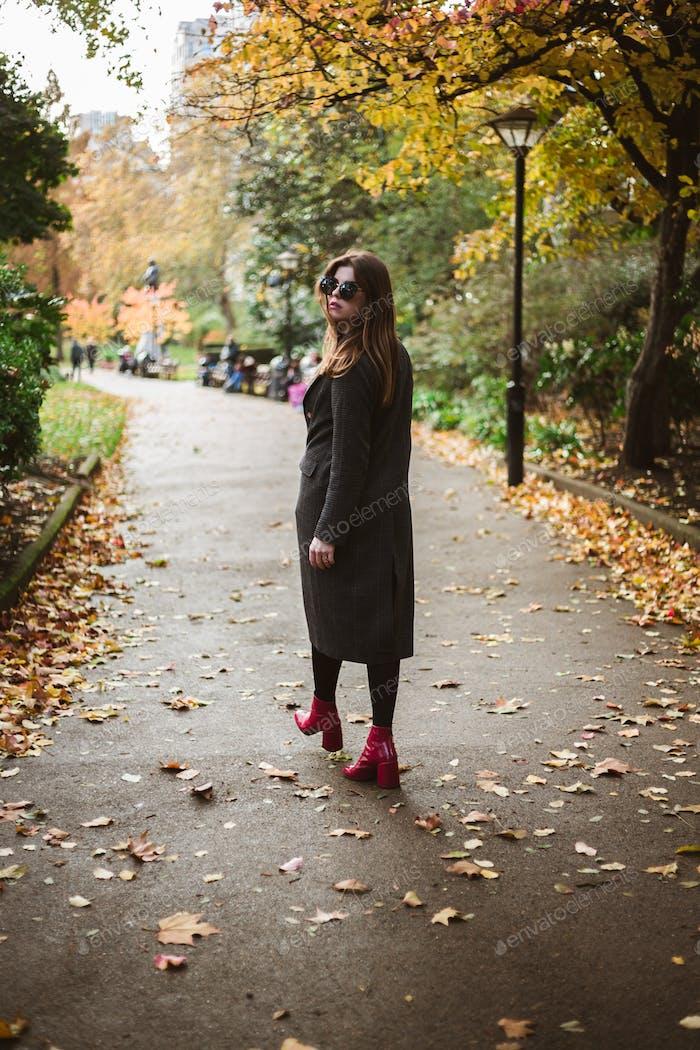 Joven bien vestida caminando por el parque