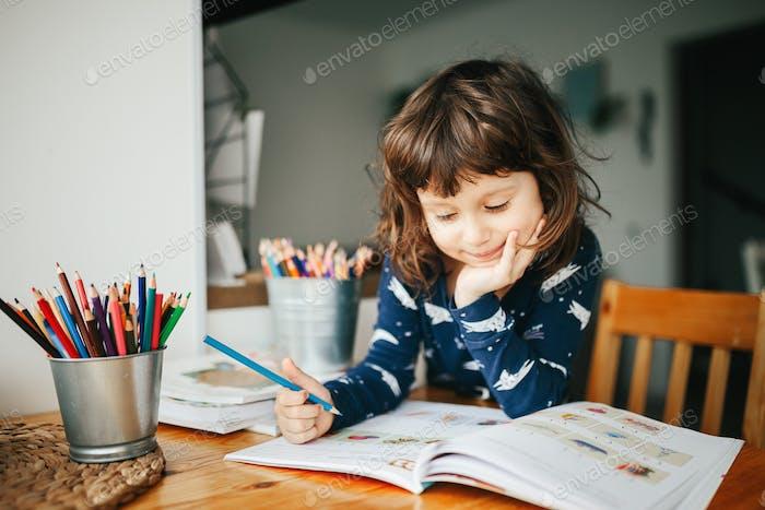 Child preschooler girl learning at home