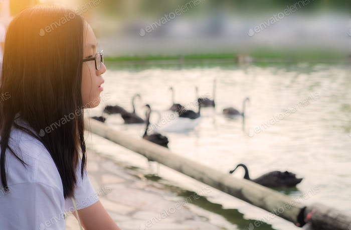 Headshot of a young Thai girl with long black hair and eyeglasses sitting at lakeside looking away
