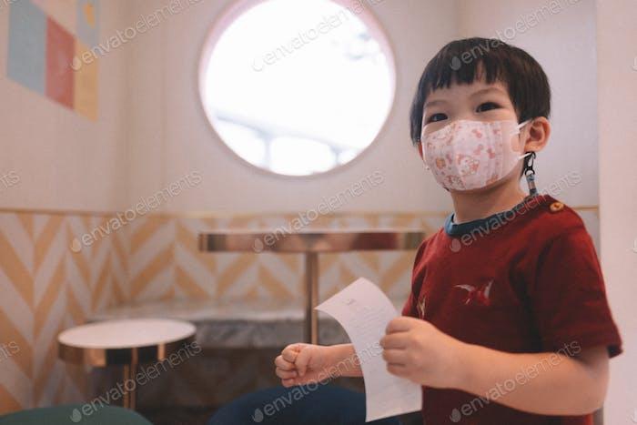 Boy in cafe holding receipt