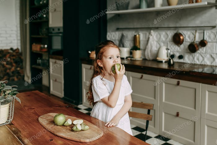 little red-haired girl in a white casual dress eats a green apple and looks away in the dark kitchen