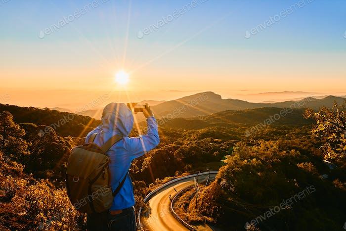 Backpacker taking a photo landscape view with sunrise, Doi Inthanon, Chiangmai, Thailand
