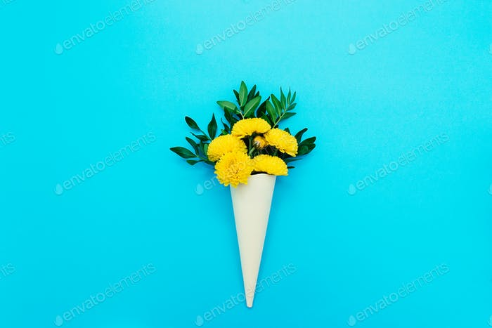 Yellow chrysanthemums in a paper cone on a blue background.Greeting card.