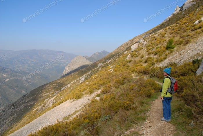 Woman on a hiking trail across a scree slope, on the Sierra Bernie, Alicante Province, Spain