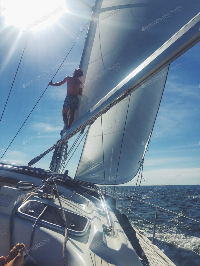 Boy on the mast of a 46 foot sailboat