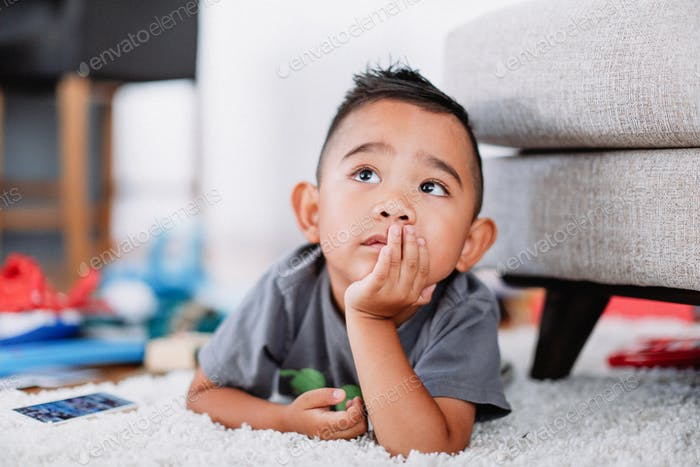 Cute young little diverse boy laying on a rug watching TV.