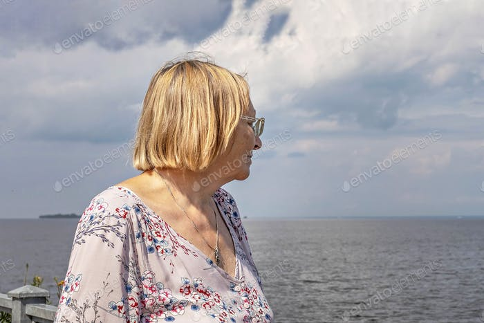 An elderly woman in a long summer dress stands on the sea embankment