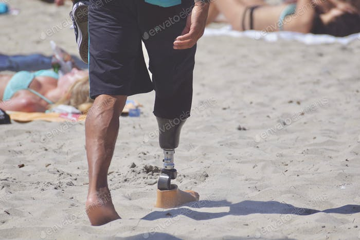 Young, man with prosthetic lower leg and foot, walking on the beach on a sunny day