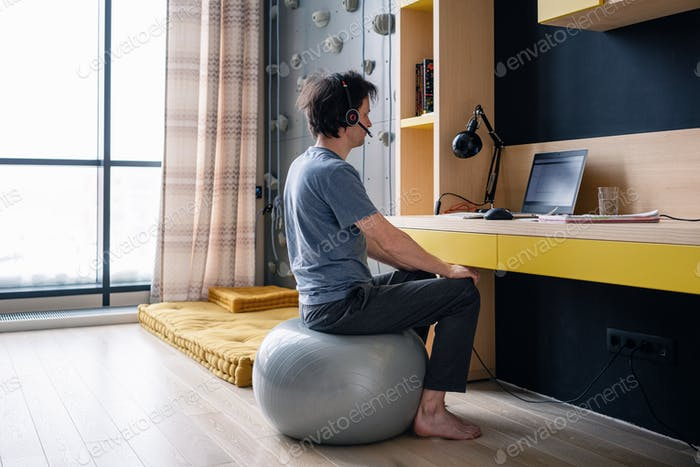 Developer or IT professional working on a yoga ball in a home office during coronavirus pandemic