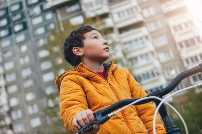 Netter Tween-Junge in gelber Jacke auf dem Fahrrad in der Stadtstraße, Herbstsaison
