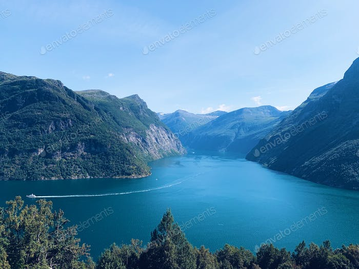 Aerial view of the Geiranger fjord in Norway, blue sky and mountain range, altitude and perspective