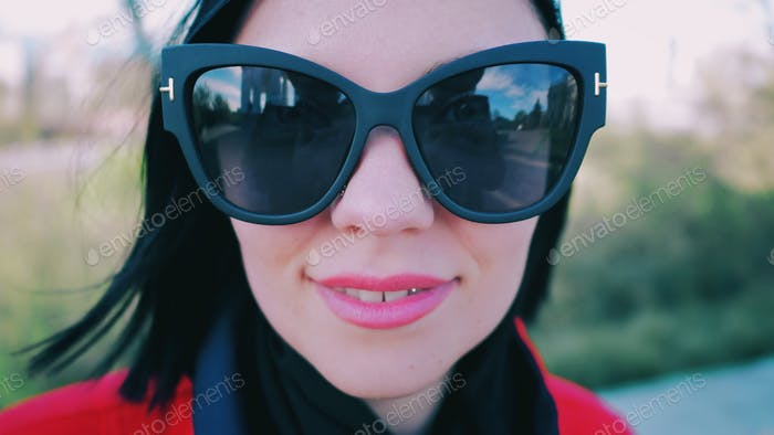 Portrait of young woman in big cat eye sunglasses