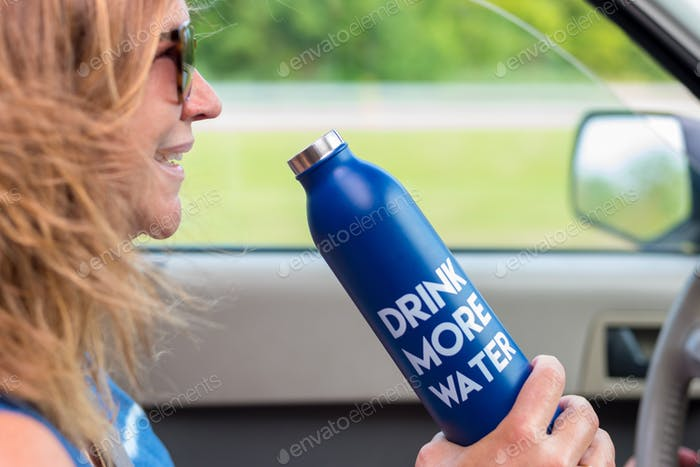 Smiling woman with water bottle driving a car, hair blowing in wind