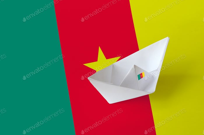 Cameroon flag depicted on paper origami ship closeup. Oriental handmade arts concept