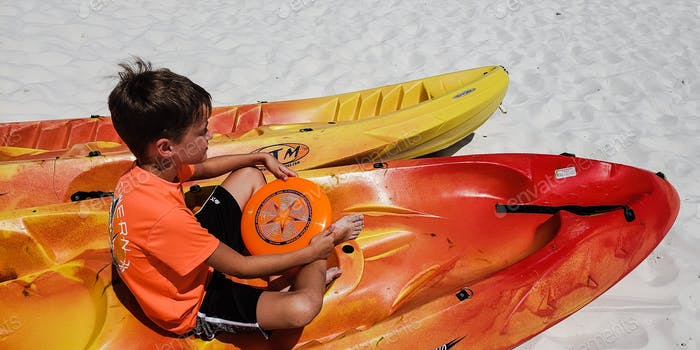 Little boy and his orange frisbee sitting in a kayak on the beach soaking in the sun on a bright and