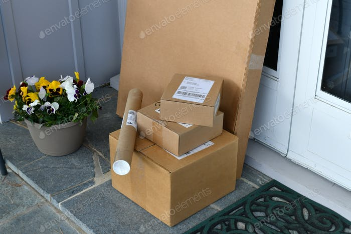 Boxes Packages mail parcels from online orders on a front porch after being delivered