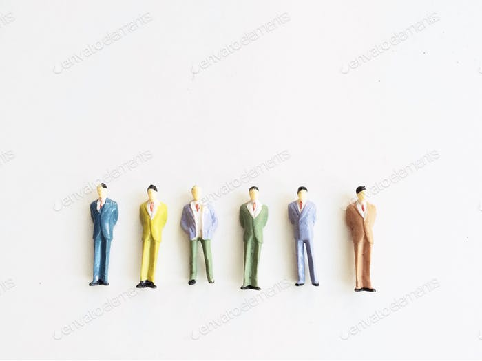 Row of six tiny model people businessmen dressed in suits centered on a white background.