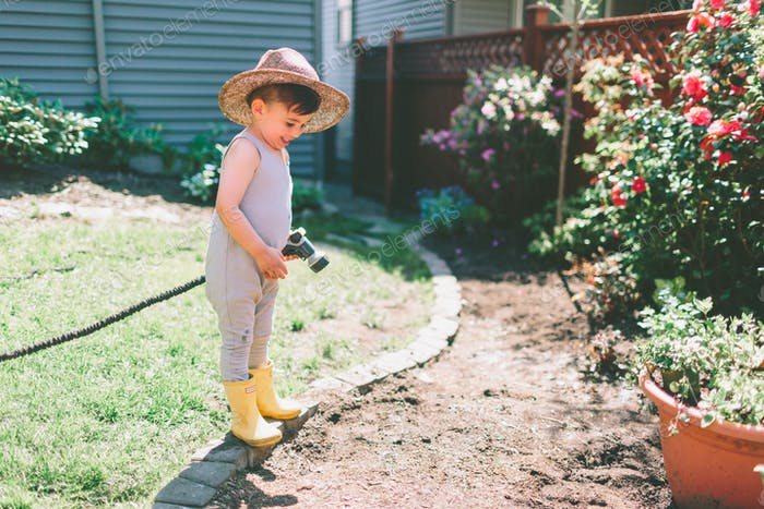 A little boy gardening with the hose in the summer.
