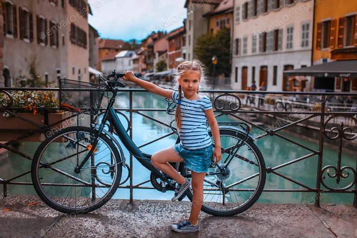 Cute girl discovering the old town of Annecy by bicycle