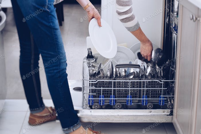 Woman unloading clean dishes from a dishwasher