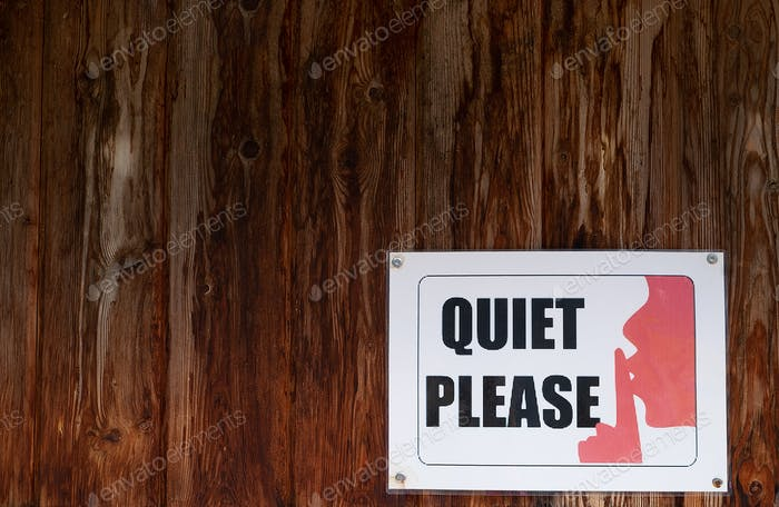 A sign on the wooden wall says Quiet Please