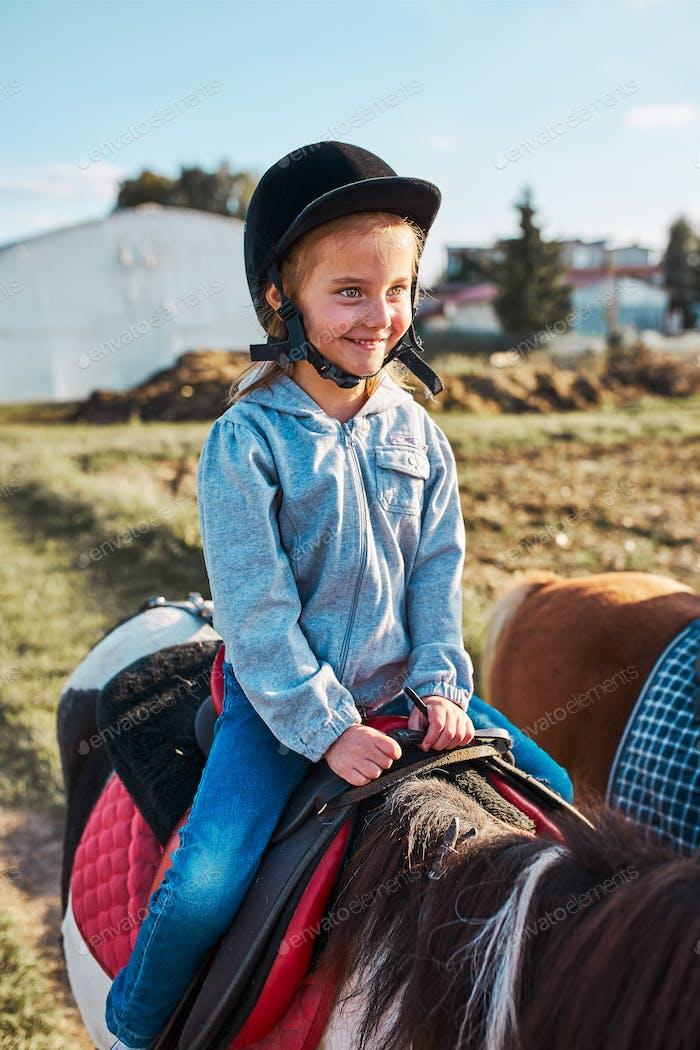Little smiling girl learning horseback riding. 5-6 years old equestrian in helmet