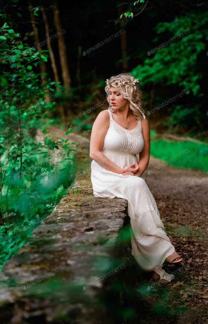 Attractive female outdoors in woods looking over her shoulder off into the distance deep in thought