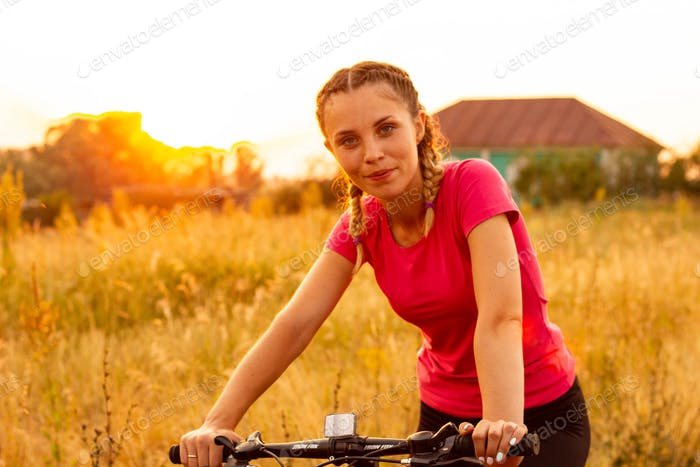 portrait of a beautiful girl sitting on a bicycle on a summer evening in the setting sun