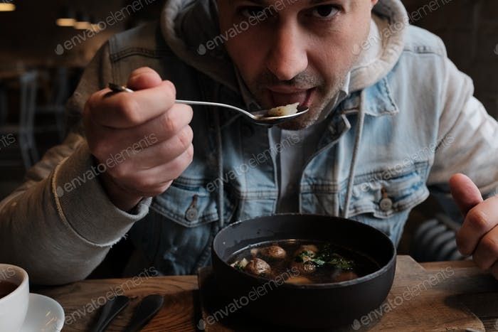 🌟Nominated🌟 man is holding the spoon while eating his yummy bowl of hot spicy soup 💲