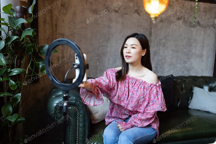Happy young asian woman influencer using technology in cafeteria or studio