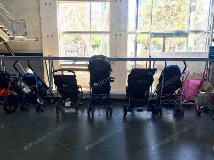 Baby strollers lined up in a row at a museum