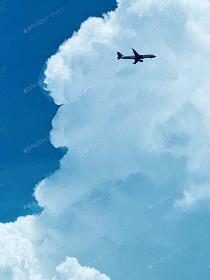 Airplane Flying Below The Cumulus Clouds